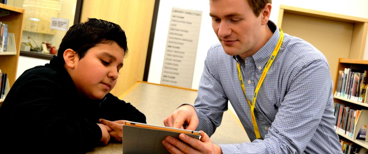Librarian helping teen patron with a tablet